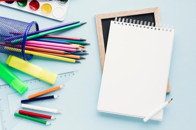 Bloc de notas en blanco junto a crayones