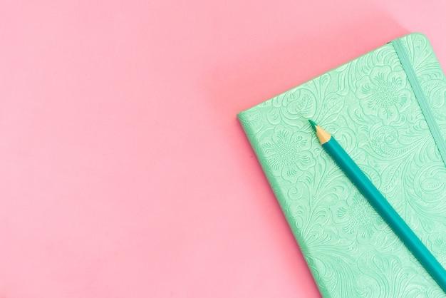 Bloc de notas en blanco con lápiz amarillo sobre fondo rosa y azul