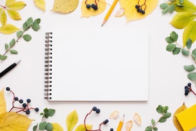 Bloc de notas en blanco en marco de hojas de otoño