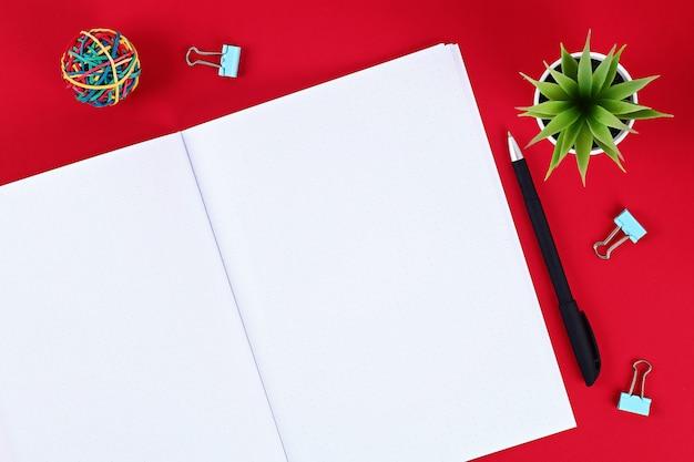 Bloc de notas en blanco en la mesa roja, planta, pluma.
