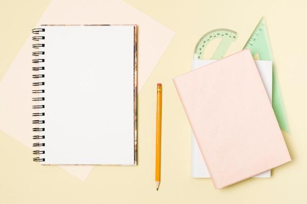 Bloc de notas en blanco de plano sobre fondo amarillo claro