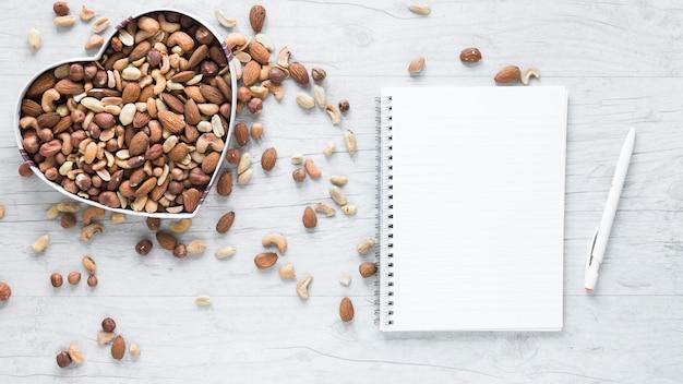 Bloc de notas en blanco y pluma con frutos secos en forma de corazón en el escritorio de madera