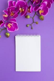Bloc de notas en blanco rodeado de orquídeas