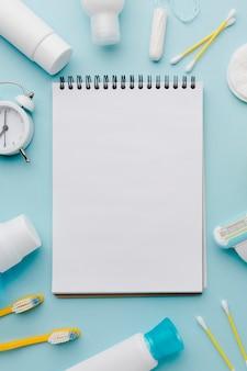 Bloc de notas en blanco rodeado de productos de higiene.