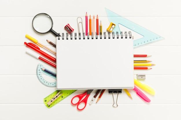 Bloc de notas en blanco rodeado de útiles escolares