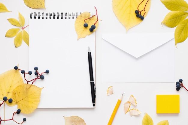 Bloc de notas en blanco y sobre en marco de hojas de otoño