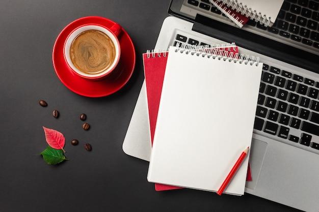 Bloc de notas en blanco sobre la taza de café y portátil en la mesa de oficina negro