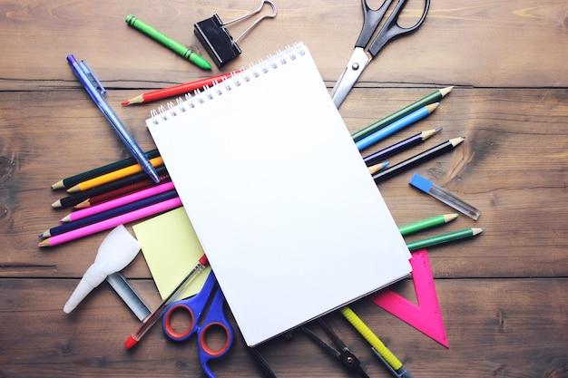 Bloc de notas en blanco sobre útiles escolares y de oficina en la mesa de oficina