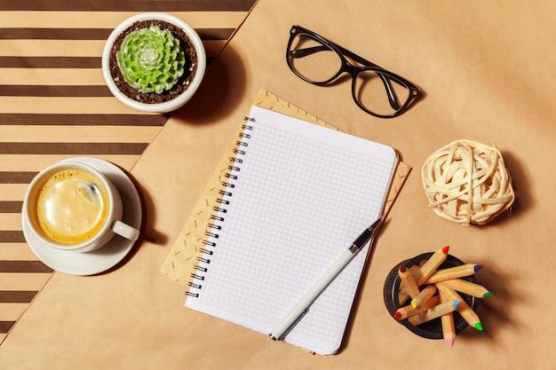 Bloc de notas en blanco y taza de café