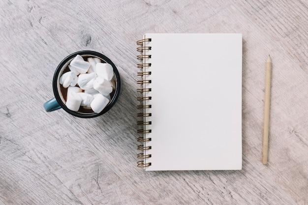 Bloc de notas en blanco con taza de malvaviscos