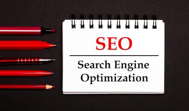 Un bloc de notas blanco con el texto seo search engine optimization, escrito en un bloc de notas blanco junto a bolígrafos, lápices y marcadores rojos sobre un fondo negro.