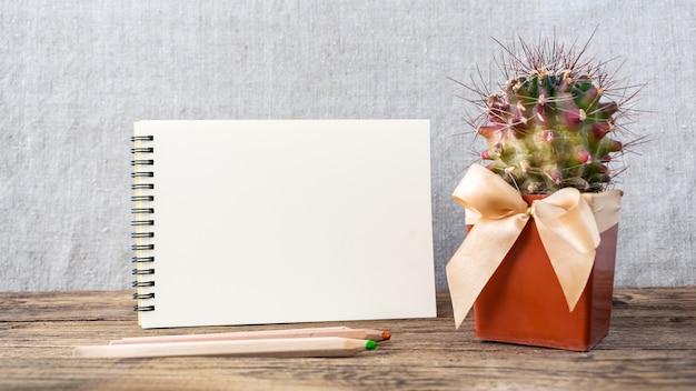 Bloc de notas blanco vacío, cuaderno, lápices de colores y cactus.