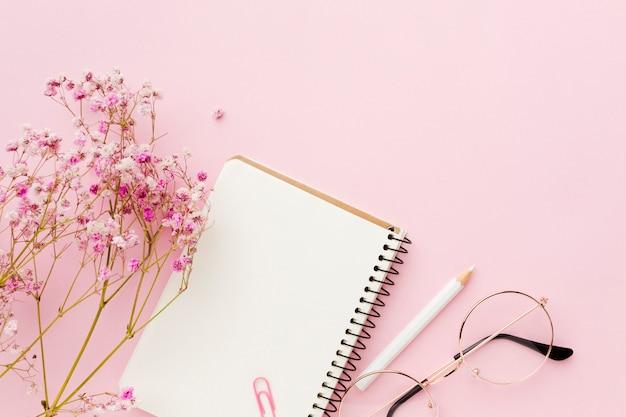 Bloc de notas blanco vacío y flores en plano