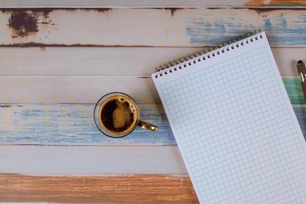 Bloc de notas con bolígrafo y café expreso en la mesa.
