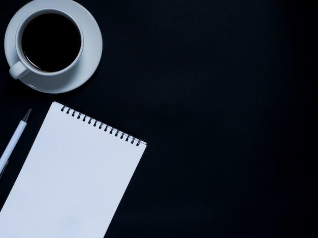 Bloc de notas, bolígrafo y café negro