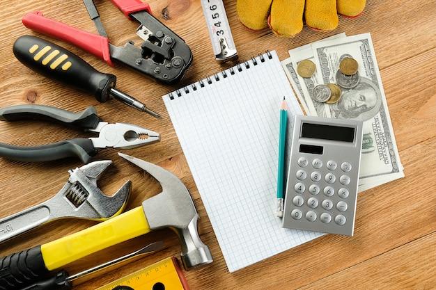 Bloc de notas y bolígrafo, calculadora y dinero, herramientas para construcción y reparación.