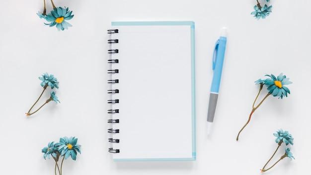 Bloc de notas y bolígrafo cerca de flores de manzanilla azul