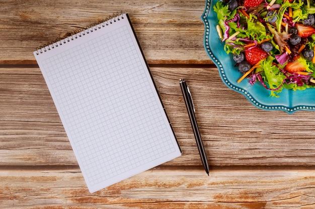 Bloc de notas y bolígrafo con ensalada en la mesa de madera