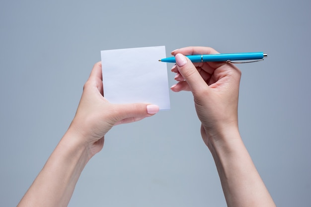 El bloc de notas y el bolígrafo en manos femeninas sobre fondo gris