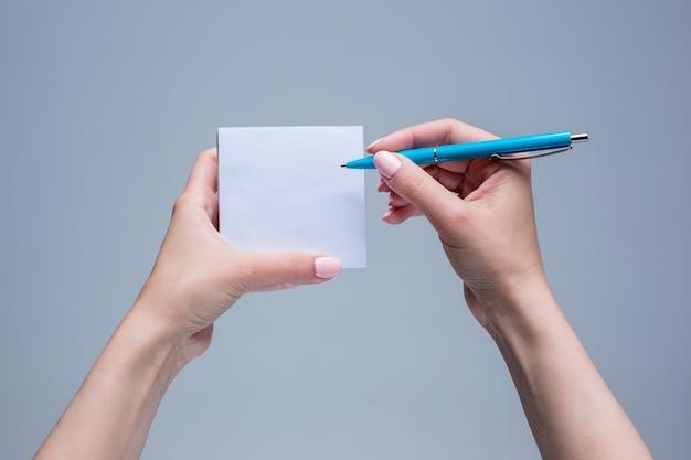 Bloc de notas y bolígrafo en manos femeninas sobre fondo gris