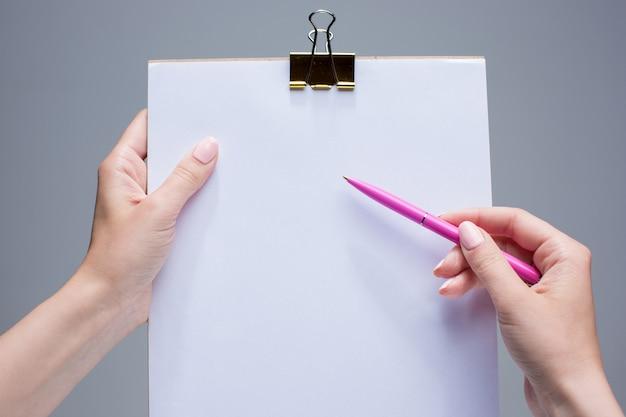 Bloc de notas y bolígrafo en manos femeninas