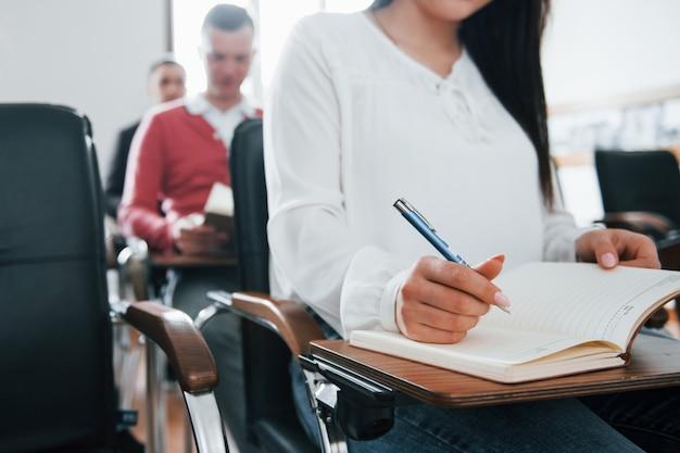 Con bloc de notas y bolígrafo en las manos. grupo de personas en conferencia de negocios en el aula moderna durante el día