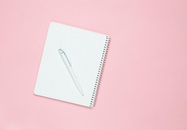 Bloc de notas con bolígrafo sobre un fondo rosa pastel, vista superior, tendencia minimalista