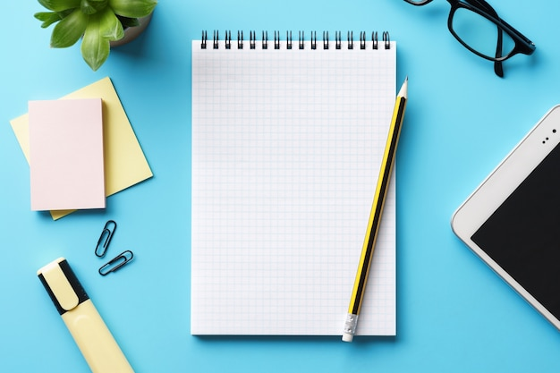 Un bloc de notas, un bolígrafo y una tableta vacíos abiertos en un escritorio azul. hacer una lista o planificar.