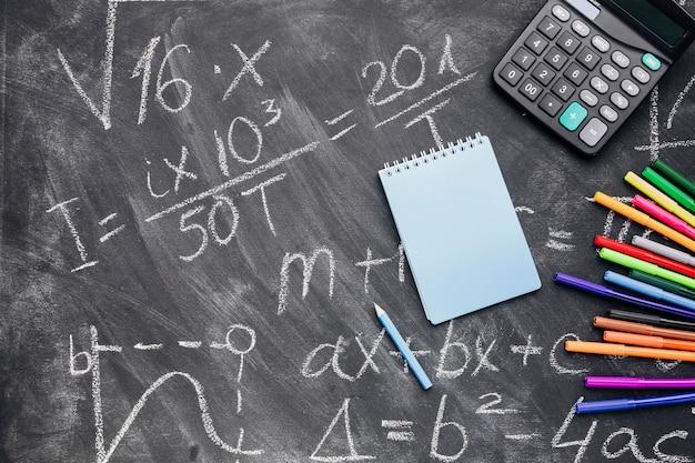 Bloc de notas y calculadora con rotuladores dispuestos en pizarra escrita