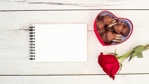 Bloc de notas cerca de caja con dulces y flores