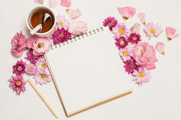 Bloc de notas cerca de conjunto de flores y taza de bebida