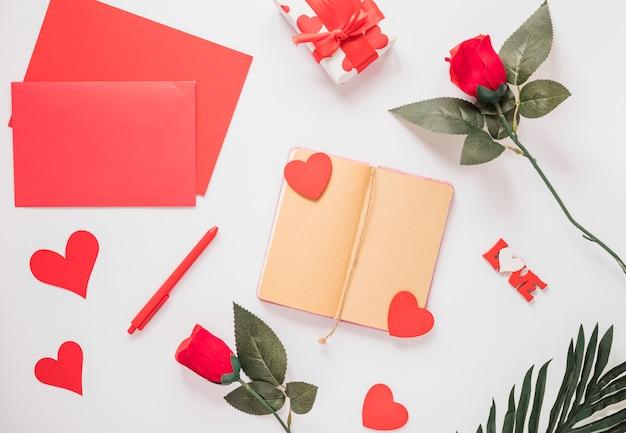 Bloc de notas cerca de papeles, adornos de corazones, flores, bolígrafo y regalo.