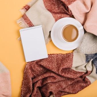 Bloc de notas cerca de taza y bufanda