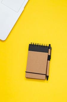 Bloc de notas y computadora sobre fondo amarillo