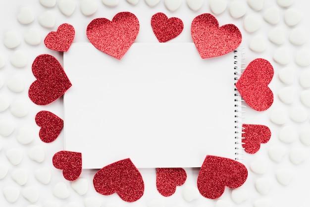 Bloc de notas entre conjuntos de adornos de corazones.