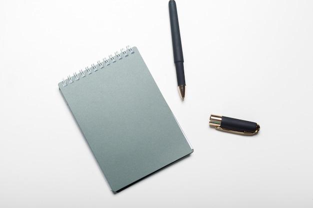 Bloc de notas cuaderno y bolígrafo aislado sobre fondo blanco.