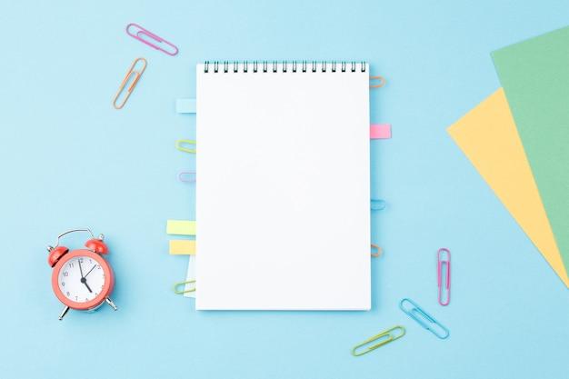 Bloc de notas escolar con papelería sobre fondo azul.