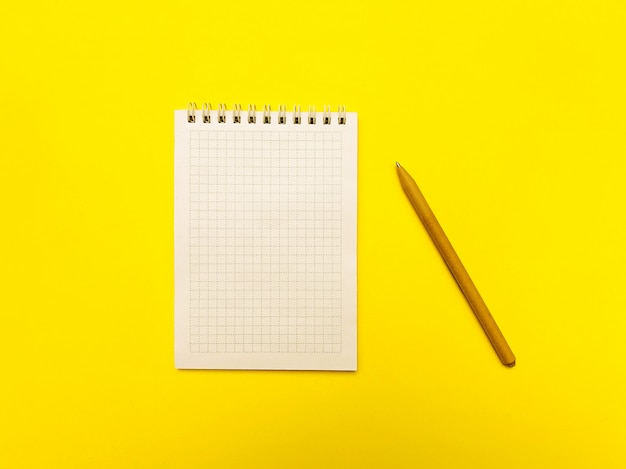Bloc de notas para escribir sobre una superficie amarilla