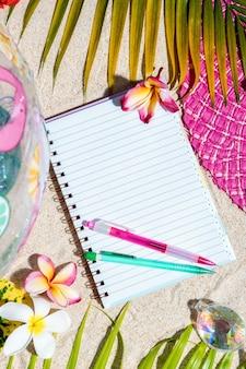 Bloc de notas de escritura en blanco abierto con lápiz rosa y verde sobre arena