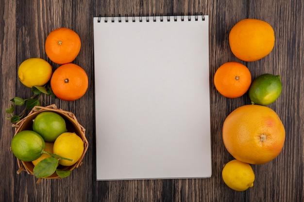 Bloc de notas de espacio de copia de vista superior con pomelo naranjas limones y limas en una canasta sobre un fondo de madera