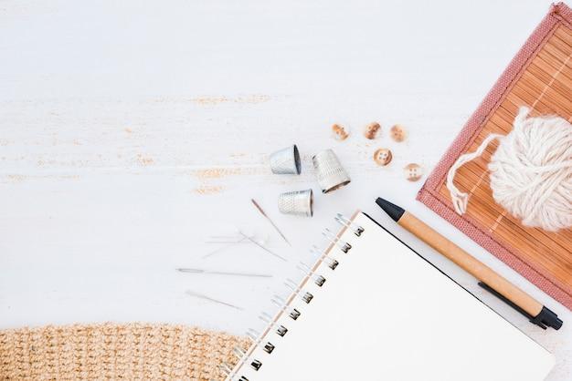 Bloc de notas en espiral; agujas dedal; botones; bolígrafo; bola de lana en mantel sobre fondo de madera con textura