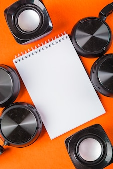 Bloc de notas de espiral blanco en blanco con auriculares y altavoz sobre un fondo naranja
