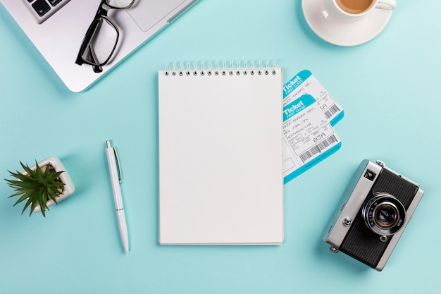 Bloc de notas de espiral en blanco con boletos aéreos rodeados con laptop, lentes, bolígrafo, cámara, taza de café en el escritorio azul