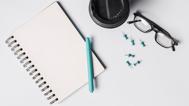 Bloc de notas espiral en blanco; bolígrafo; taza de café; anteojos y marcadores sobre fondo blanco