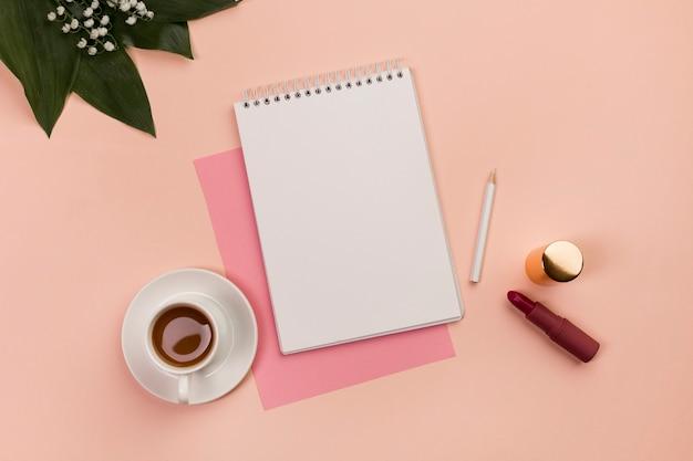 Bloc de notas espiral en blanco, lápiz, lápiz labial, taza de café y hojas sobre fondo de melocotón