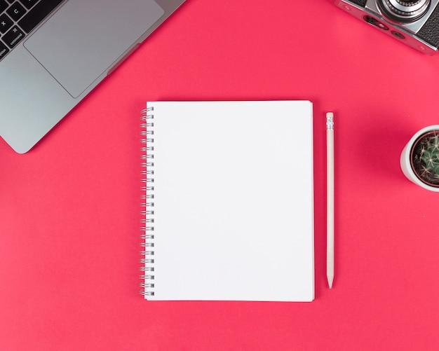 Bloc de notas espiral en blanco con lápiz de madera; ordenador portátil; cámara y planta de cactus sobre fondo brillante.