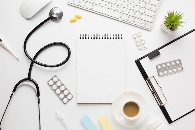 Bloc de notas espiral en blanco y portapapeles dispuestos en escritorio médico con taza de café
