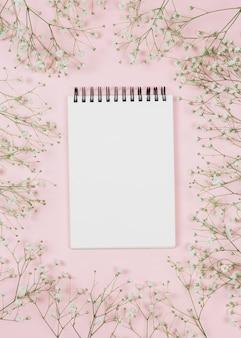 Bloc de notas espiral en blanco rodeado de flores de gypsophila sobre fondo rosa