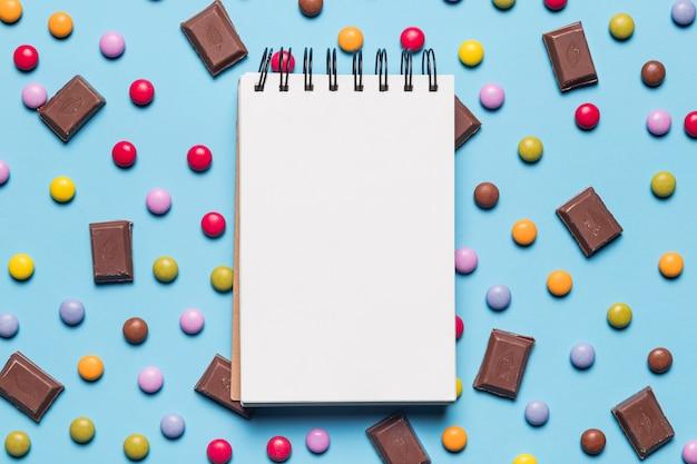 Bloc de notas de espiral en blanco sobre los caramelos de gema y piezas de chocolate sobre fondo azul