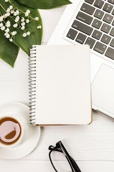 Bloc de notas espiral en blanco en la taza de café y portátil con hojas y flores en el escritorio